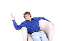 El adolescente se sienta en silla Imagen de archivo