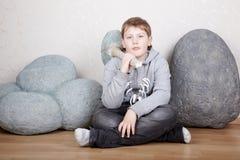El adolescente se sienta en suelo laminado con un hacha de piedra Fotografía de archivo libre de regalías
