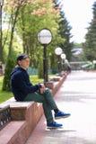 El adolescente se sienta en un banco en un parque del verano Foto de archivo libre de regalías