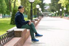 El adolescente se sienta en un banco en un parque del verano Foto de archivo