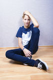 El adolescente se sienta en un piso en el cuarto Foto de archivo