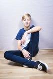 El adolescente se sienta en un piso en el cuarto Fotografía de archivo