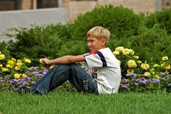 El adolescente se sienta en una hierba Imagen de archivo libre de regalías