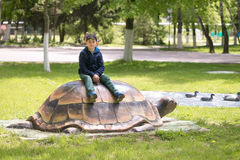 El adolescente se sienta en una tortuga en un parque del verano Imagen de archivo