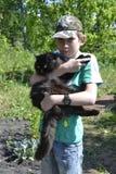 El adolescente se sostiene en las manos de un gato mullido negro Imágenes de archivo libres de regalías