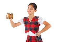El adolescente se vistió con ropa de la tela escocesa y la taza rojas de cerveza Imagenes de archivo