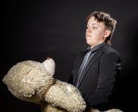 El adolescente se vistió en el traje con su juguete viejo - peluche-oso Fotos de archivo libres de regalías