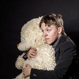 El adolescente se vistió en el traje con su juguete viejo - peluche-oso Imagen de archivo