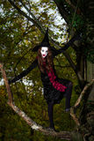 El adolescente se vistió en el traje de la bruja que se sentaba en el árbol Imagen de archivo
