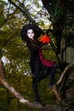 El adolescente se vistió en el traje de la bruja que se sentaba en el árbol Foto de archivo libre de regalías