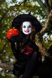 El adolescente se vistió en el traje de la bruja que se sentaba en el árbol Imagenes de archivo