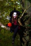 El adolescente se vistió en el traje de la bruja que se sentaba en el árbol Fotografía de archivo libre de regalías
