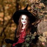 El adolescente se vistió en el traje de la bruja que se sentaba en el árbol Foto de archivo