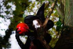 El adolescente se vistió en el traje de la bruja que se sentaba en el árbol Fotos de archivo