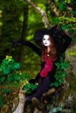El adolescente se vistió en el traje de la bruja que se sentaba en el árbol Fotografía de archivo