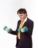 El adolescente se vistió en el traje de la oficina que hacía ejercicios del deporte Imagen de archivo libre de regalías