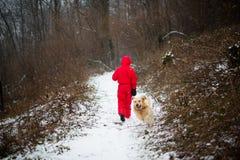 el adolescente se vistió en paseos rojos del color del invierno en trayectoria nevosa en Foto de archivo