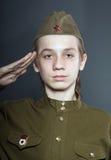 El adolescente se vistió en uniforme del soviet Imagenes de archivo