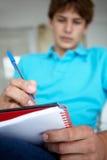 El adolescente sentó la escritura en cuaderno Foto de archivo