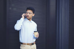 El adolescente serio atractivo se vistió en la ropa de moda que tenía conversación con el amigo Foto de archivo libre de regalías
