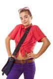El adolescente sonriente con el bolso y las gafas de sol encoge su hombro Fotos de archivo