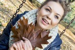 El adolescente sonriente con el roble marrón se va en las manos Imagen de archivo
