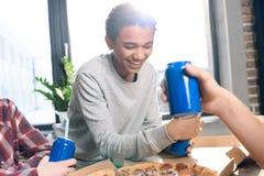 El adolescente sonriente con soda bebe y los amigos cerca cerca Fotos de archivo