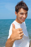 El adolescente sonriente contra el mar muestra gesto del ?? Imagen de archivo