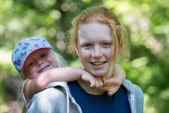 El adolescente sonriente da a hermana más joven un transporte por ferrocarril Fotografía de archivo libre de regalías