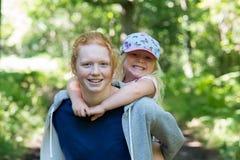 El adolescente sonriente da a hermana más joven un transporte por ferrocarril Foto de archivo libre de regalías