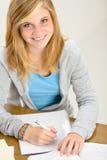 El adolescente sonriente del estudiante que se sienta detrás del escritorio escribe Imagen de archivo