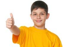 El adolescente sonriente demuestra el pulgar para arriba Fotografía de archivo