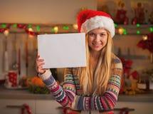 El adolescente sonriente en el sombrero de santa que muestra el papel en blanco cubre Fotografía de archivo