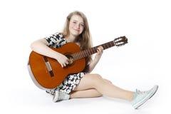 El adolescente sonriente en vestido toca la guitarra que se sienta en la f Imágenes de archivo libres de regalías
