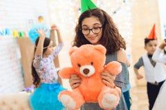 El adolescente sonriente en vidrios está sosteniendo el oso de peluche en manos Partido del feliz cumpleaños Fotografía de archivo