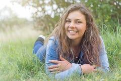 El adolescente sonriente está mintiendo en la hierba Foto de archivo libre de regalías