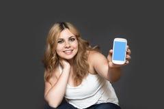 El adolescente sonriente está mostrando su teléfono elegante Imagen de archivo libre de regalías