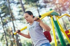 El adolescente sonriente hace ejercicios en el simulador en parque Imagenes de archivo