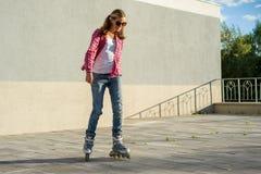 El adolescente sonriente joven de la muchacha se divierte en pcteres de ruedas al aire libre H Imagen de archivo