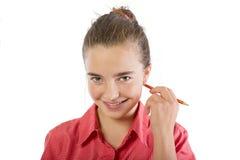 El adolescente sonriente rasguña con un lápiz detrás del oído, isola Imágenes de archivo libres de regalías