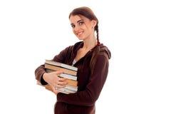 El adolescente sonriente se coloca oblicuo y guarda los libros Fotografía de archivo libre de regalías