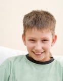 El adolescente sonriente se sienta en el país Imagen de archivo libre de regalías
