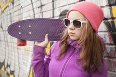 El adolescente sostiene el monopatín cerca al lado de la pared urbana Fotografía de archivo