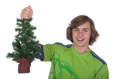 El adolescente sostiene en una mano un piel-árbol de la Navidad Imágenes de archivo libres de regalías