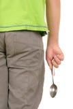 El adolescente sostiene la cuchara Imagen de archivo libre de regalías