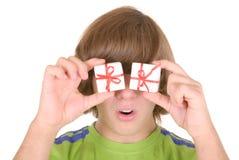 El adolescente sostiene los regalos antes de ojos Imagenes de archivo