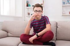 El adolescente tiene charla del teléfono en sala de estar en casa Imagen de archivo
