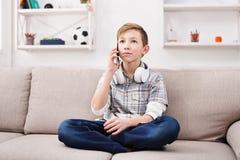 El adolescente tiene charla del teléfono en sala de estar en casa Foto de archivo libre de regalías