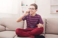 El adolescente tiene charla del teléfono en sala de estar en casa Imágenes de archivo libres de regalías