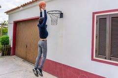 El adolescente tira el baloncesto hacia el aro montado sobre la puerta del garaje fotografía de archivo